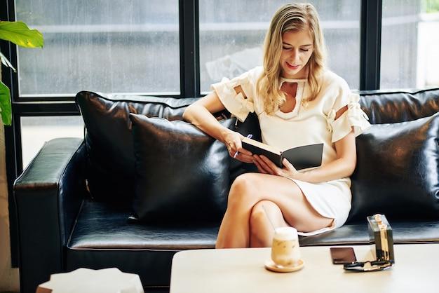 Улыбается довольно элегантная молодая женщина, читающая интересную книгу в кафе