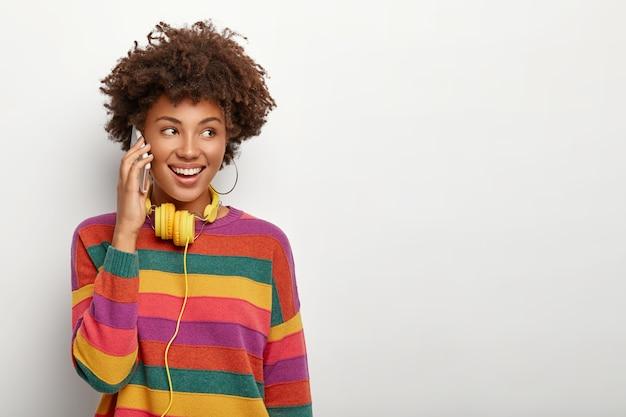 La donna graziosa sorridente ha una conversazione telefonica, essendo di ottimo umore durante una bella chiacchierata, tiene lo smartphone vicino all'orecchio, indossa un maglione casual, utilizza le cuffie, isolato su bianco