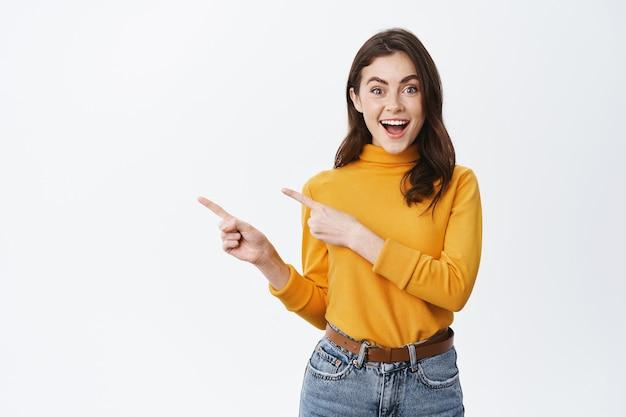 空きスペースに残された指を指して、白い壁に広告を表示して、それをチェックするように誘うきれいな女性モデルの笑顔