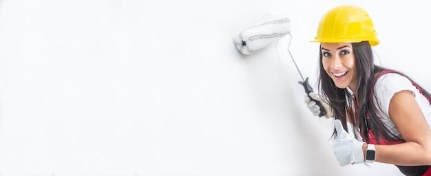 Улыбающаяся симпатичная женщина в шлеме красит стену белым валиком, показывая палец вверх.