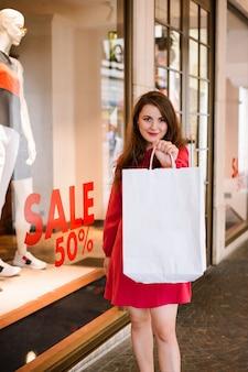 예쁜 소녀 미소, 카메라를 찾고 복사 공간이있는 흰색 쇼핑백 표시, 쇼핑 개념