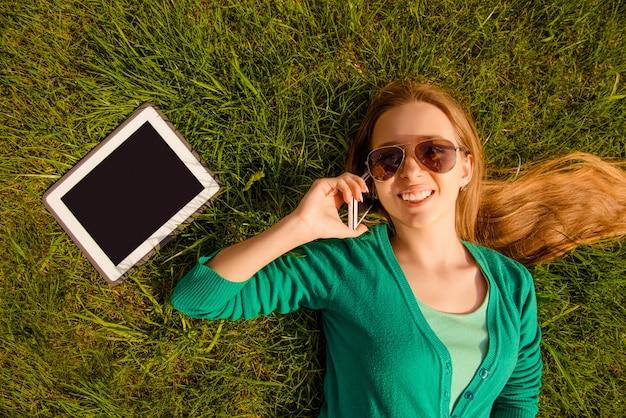 Улыбающаяся красивая девушка лежит на траве и разговаривает по телефону