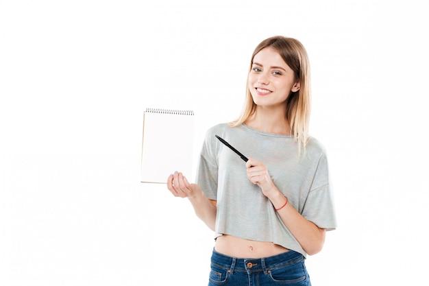 Усмехаясь милая девушка указывая ручка на тетради чистого листа бумаги