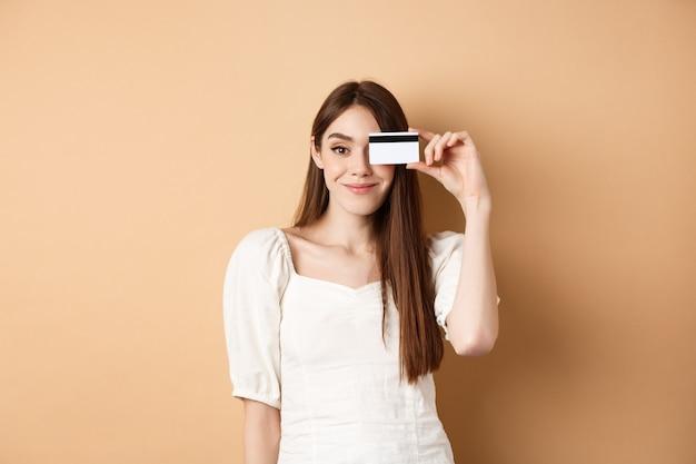 目の上にプラスチックのクレジットカードを示し、ベージュのバックの上に立って満足そうに見えるかわいい女の子の笑顔...