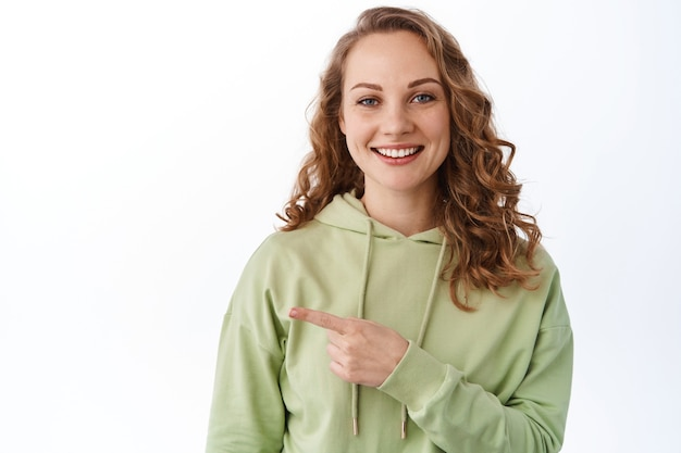 巻き毛の金髪のかわいい女の子を笑顔、指を脇に向け、コピースペースのプロモーションテキストを表示し、白い壁に緑のパーカーで立っています