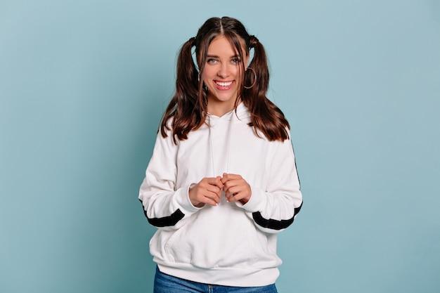 긍정적 인 뉴스를 즐기고, 즐겁고 매력적인 미소로 카메라를 바라보고있는 검은 물결 모양의 머리에 예쁜 소녀를 웃고 있습니다. 실내 휴식 학생 소녀