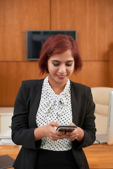Smiling pretty indian businesswoman answering text messages on her smartphone