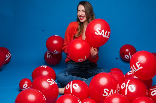 Smiling pretty lady holding two red balloons in , isolated on blue wall
