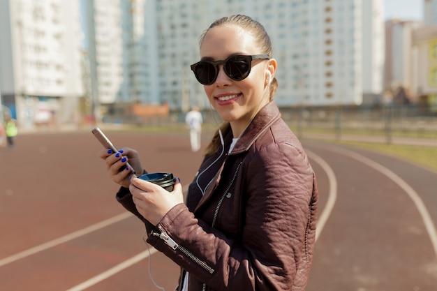Улыбающаяся красивая дама с темной прической в солнцезащитных очках использует смартфон и слушает музыку
