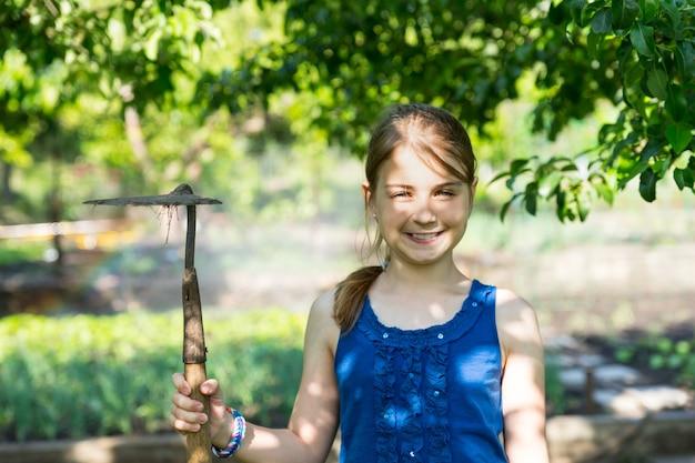 彼女は春の菜園の木陰に立っている鍬を持って笑顔のかわいい女の子
