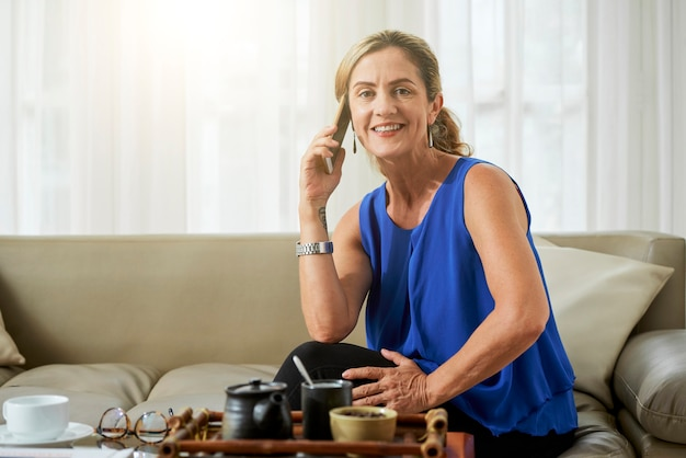 웃고 있는 꽤 성숙한 여성이 소파에 앉아 차를 마시고 전화 통화를 하고 카메라를 보며 웃고 있습니다.