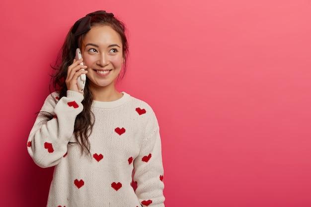 Sorridente donna di razza mista piuttosto parla al cellulare, discute di quello che è successo durante il giorno con la madre, ha un aspetto felice, indossa un maglione bianco