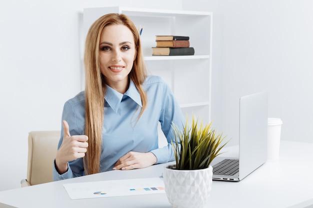 좋은 느낌과 그녀의 손가락을 들고 웃는 예쁜 사무실 여자.