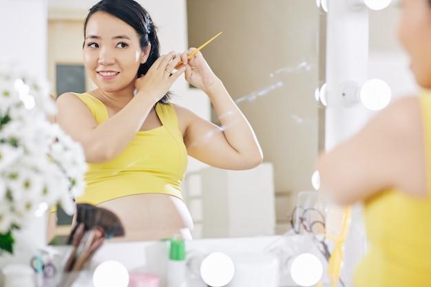 예쁜 임신 아시아 여자 화장실에서 거울에 서서 그녀의 머리를 솔질 웃고