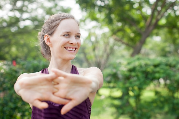 Smiling pretty sporty girl stretching clasped hands