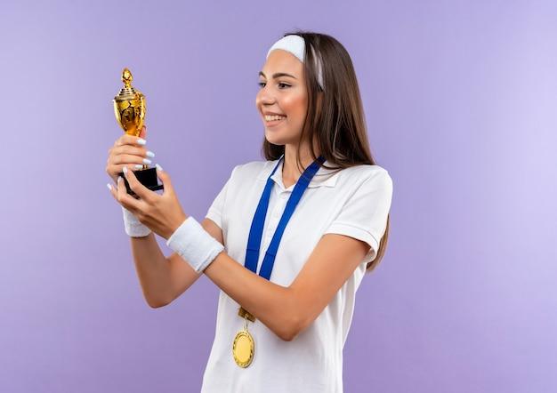 머리띠와 팔찌와 메달을 입고 보라색 공간에 고립 된 컵을보고 웃는 예쁜 스포티 한 소녀