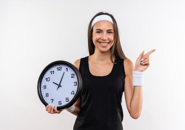 Улыбающаяся симпатичная спортивная девушка с ободком и браслетом держит часы и указывает на сторону, изолированную на белом пространстве
