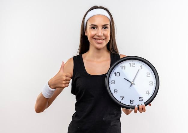 Улыбающаяся симпатичная спортивная девушка с повязкой на голову и браслетом держит часы и показывает палец вверх изолированной на белом пространстве