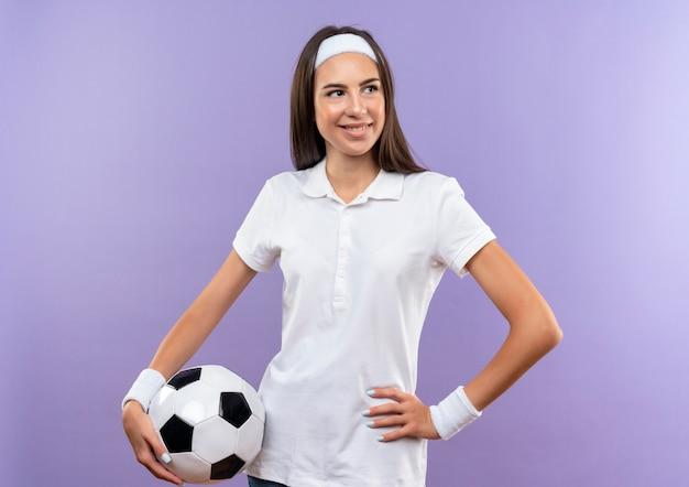 보라색 공간에 고립 된 허리에 손으로 측면을보고 축구 공을 들고 머리띠와 팔찌를 입고 꽤 스포티 한 소녀 미소