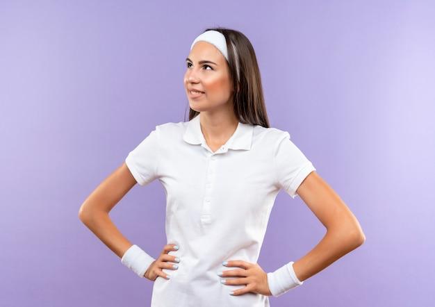 보라색 공간에 고립 된 허리에 손으로 측면을보고 머리띠와 팔찌를 입고 꽤 스포티 한 소녀 미소