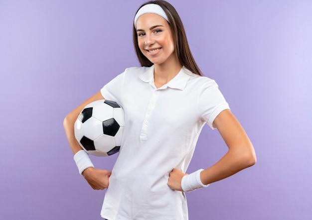 보라색 공간에 고립 된 허리에 손을 댔을 축구 공 머리띠와 팔찌를 입고 꽤 스포티 한 소녀 미소