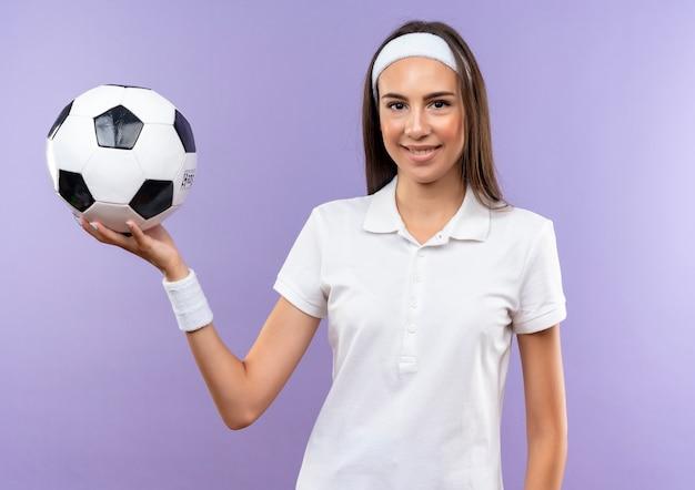 Sorridente ragazza abbastanza sportiva che indossa la fascia e il braccialetto tenendo il pallone da calcio isolato su spazio viola