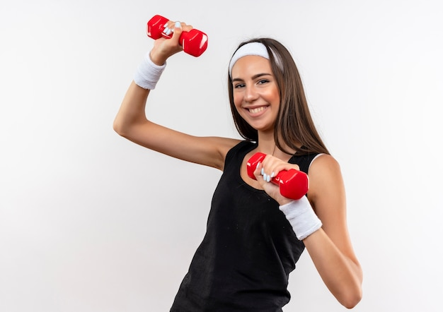 Smiling pretty sporty girl wearing headband and wristband raising dumbbells isolated on white space