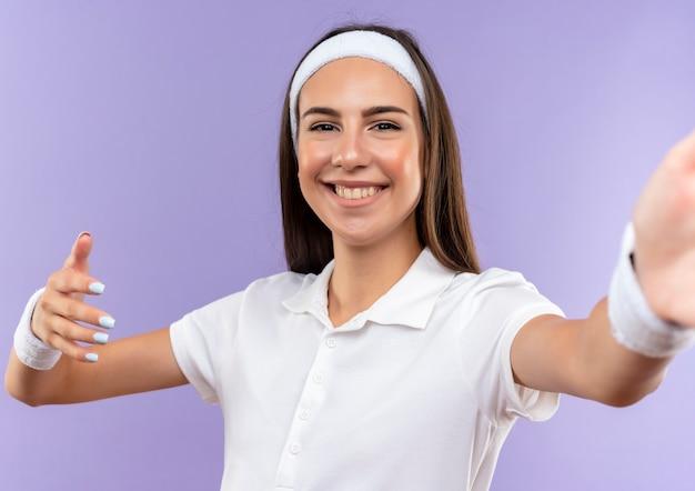 Sorridente ragazza piuttosto sportiva che indossa la fascia e il braccialetto con la mano alzata isolato su spazio viola