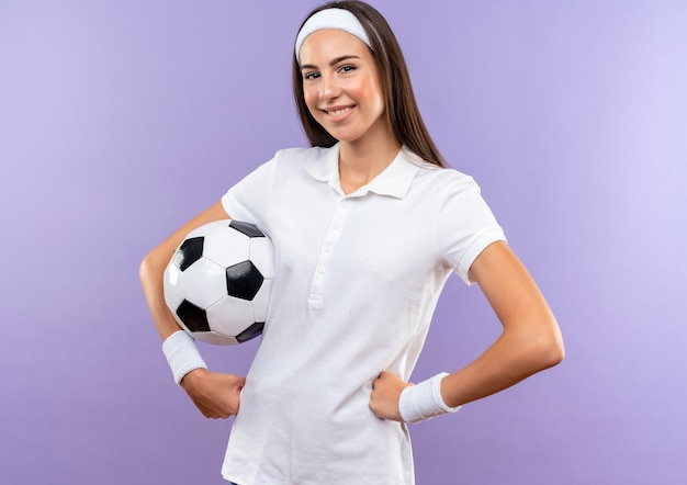 Sorridente ragazza piuttosto sportiva che indossa la fascia e il braccialetto con il pallone da calcio che mette le mani sulla vita isolata sullo spazio viola