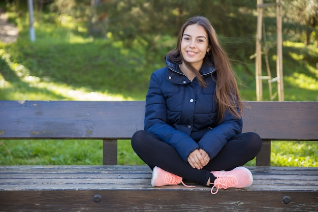 Smiling pretty sporty woman posing at camera on bench