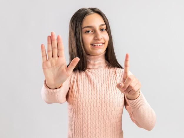 Улыбающаяся симпатичная девочка-подросток, смотрящая на фронт, показывает стоп и удерживает жесты, изолированные на белой стене