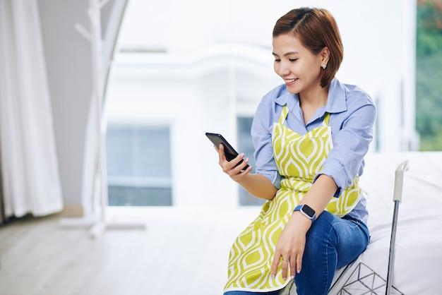 Улыбающаяся симпатичная вьетнамская домохозяйка сидит на краю кровати и проверяет текстовые сообщения в своем смартфоне