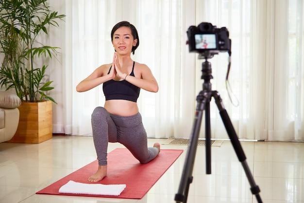 웃고 있는 예쁜 베트남 여성이 엉덩이의 유연성을 높이기 위해 낮은 라운지에서 자신을 촬영하도록 카메라를 설정했습니다.