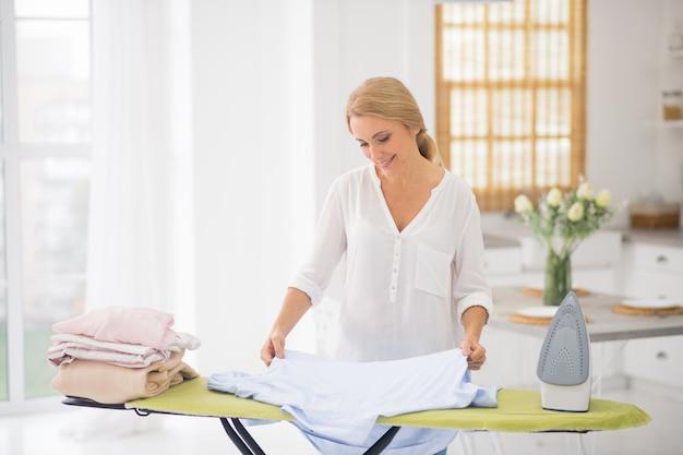 집에서 다리미판에 눈 흰 셔츠를 감탄스럽게보고 웃는 예쁜 여자