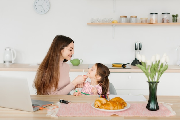 Smiling pretty woman doing make up while sitting with her little daughter at the kitchen during breakfast.
