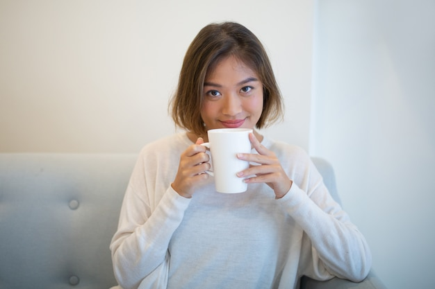 Smiling pretty woman drinking tea and sitting on couch at home