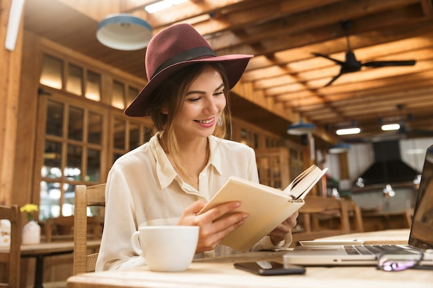 Smiling pretty woman in hat sitting at the cafe table indoors