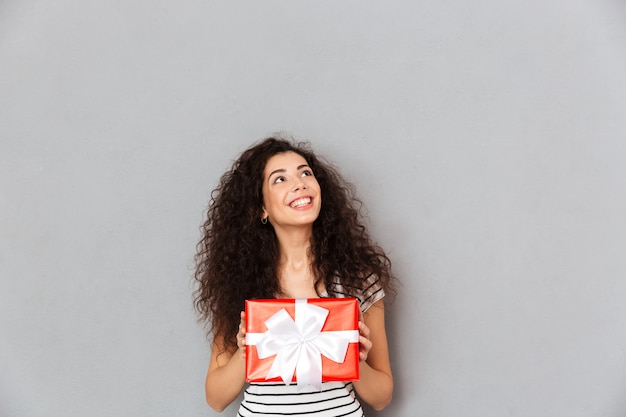 Smiling pretty woman holding gift wrapped box feeling pleasure to receive present on new year eve