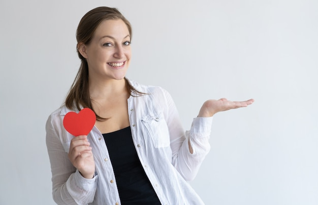 Smiling pretty woman holding paper heart and empty space