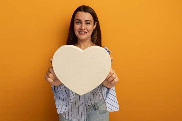 Улыбающаяся красивая женщина протягивает форму сердца, изолированную на оранжевой стене