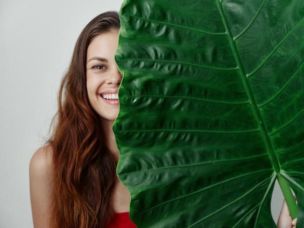 水着で笑顔のきれいな女性は、ヤシの葉のスタジオの明るい背景で彼女の顔の半分をカバーしています