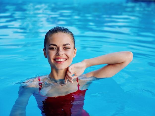 プールできれいな女性の笑顔赤い水着レクリエーション自然