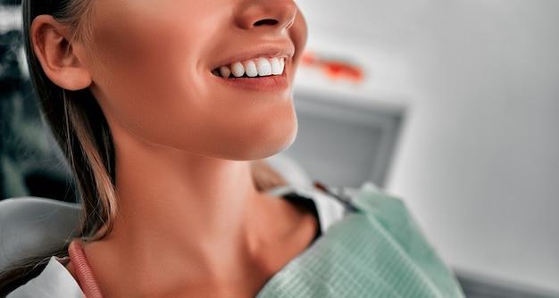 웃는 예쁜 여자가 병원에서 치과의사에게 이빨을 검사받고 있다. 치과 의사 사무실에서 치과 의자에 앉아 행복 한 젊은 여자.