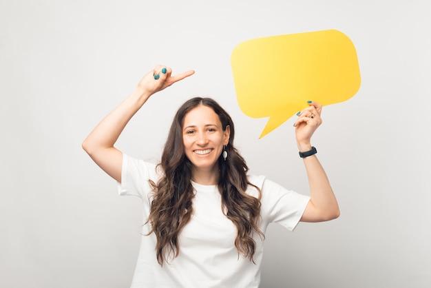Улыбающаяся красивая женщина держит желтый пузырь с речью и указывает на нее.