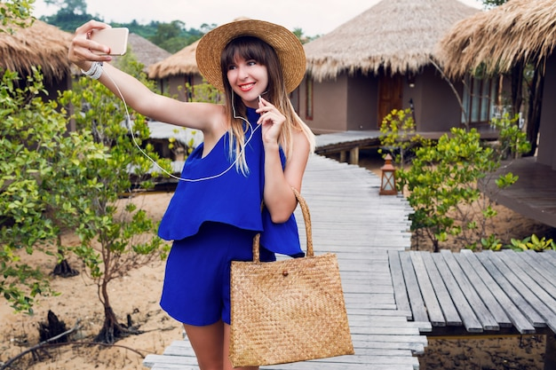 Smiling pretty woman making self portrait by mobile phone on her tropical vacation in thailand. summer bright blue clothes^ straw trendy hat and bag. red lips. happy mood.