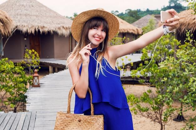 タイでの熱帯の休暇に携帯電話でセルフポートレートを作る笑顔のきれいな女性。夏の明るい青い服^ストローの流行の帽子とバッグ。赤い唇。幸せな気分。