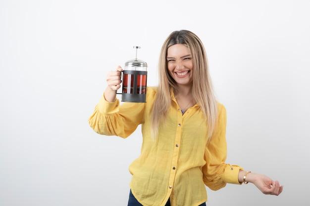 Smiling pretty woman model holding a teapot.