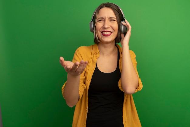 ヘッドフォンできれいな女性の笑顔は緑の壁で隔離の手を開いた
