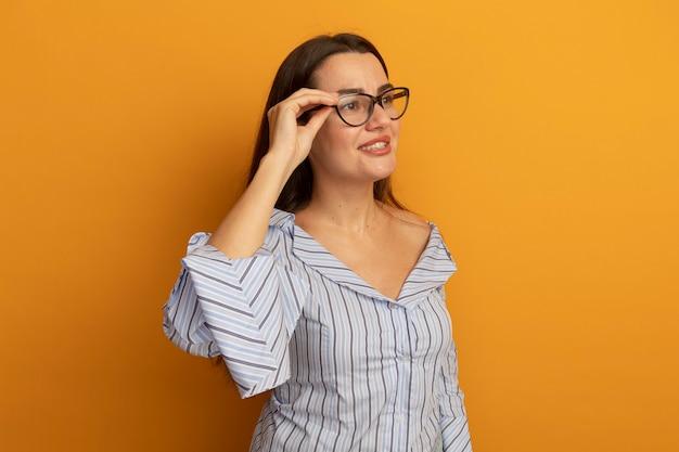 La donna graziosa sorridente in vetri ottici esamina il lato isolato sulla parete arancione
