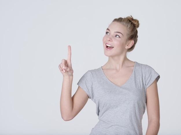 Улыбается красивая женщина указывая пальцем вверх на сером фоне. глядя в камеру